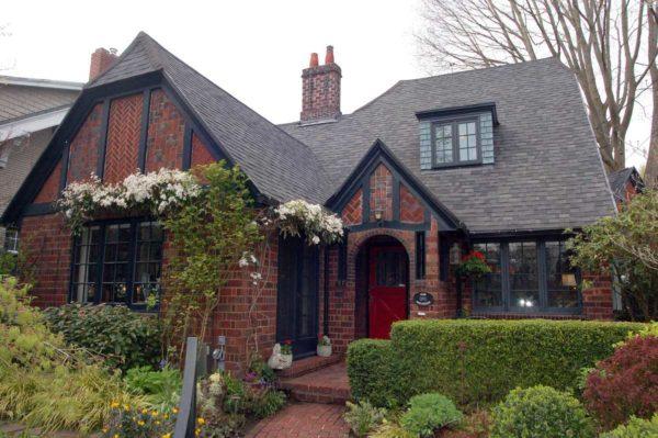 Красный кирпич разных оттенков и темно-коричневые балки, остроконечная крыша с жилыми помещениями...